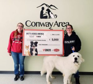 Two CAHS adoption counselors stand with a dog and an oversized $5000 check to signify our recognition as a top shelter.